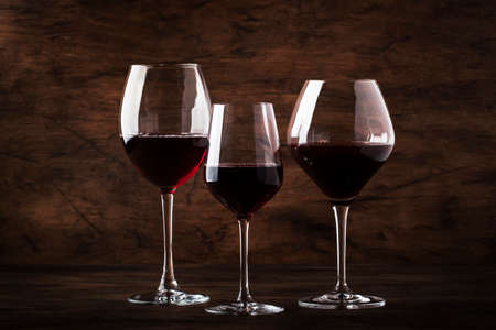 Selection of red wine on wine tasting. Dry, semi-dry, sweet red wines in special wine glasses on old wooden table background. Copy space