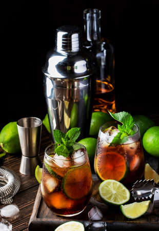 Cuba libre or rum cola cocktail with strong alcohol, lemon juice, lime and ice, dark background, steel bar tools, copy space