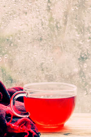 Cup with hot red tea in front of a window with water drops in rainy weather, selective focus