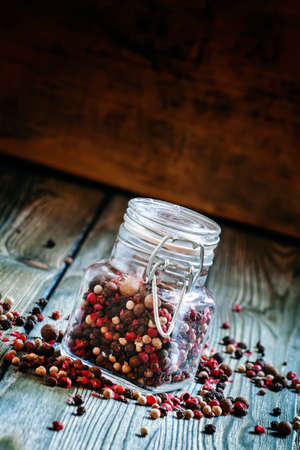 Mix from five peppers in a glass jar on old wooden table, selective focus