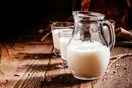 Fresh cow's milk in glass jug, vintage wooden background, still life in rustic style, selective focus