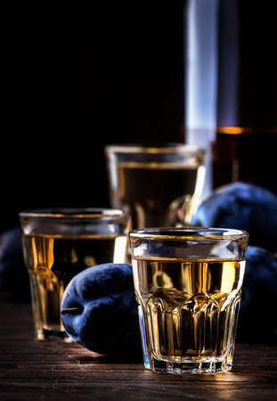 Slivovica - plum brandy or plum vodka, hard liquor, strong drink in glasses on old wooden table, fresh plums, copy space Standard-Bild