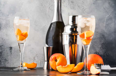 Bellini, alcoholic cocktail with sparkling wine, sugar syrup, lemon juice, peach and ice, gray table background, copy space