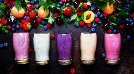 Healthy and useful colorful berry smoothies with yogurt, fresh fruit and raw berries on brown background, top view Reklamní fotografie