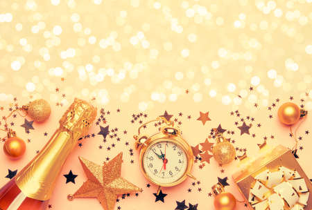 Christmas or New Year composition, frame, pink background with gold Christmas decorations, stars, snowflakes, balls, alarm clock, gift box and bottle of champagne, top view Archivio Fotografico