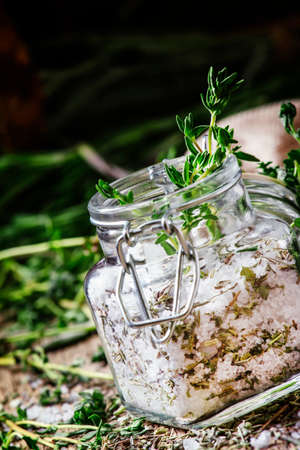 Traditional spicy salt with thyme in a glass jar, vintage wooden background, selective focus