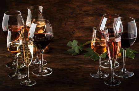 Wine tasting, still and sparkling wines. Red, white wine, rose and champagne pcs assortment in wine glasses on vintage wooden table background