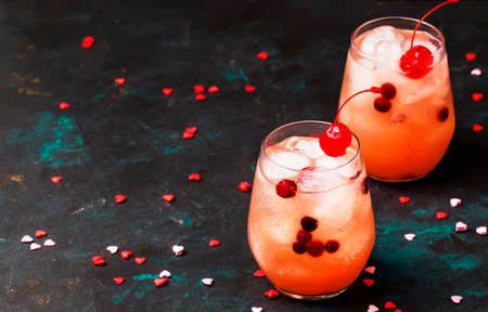 Festive pink cold alcoholic cocktail with red maraschino cherries for Valentines day, two glasses, black background with sweet red hearts, selective focus