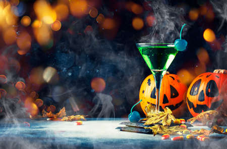 Halloween composition with festive drink, green cocktail and pumpkins lanterns, smoke and fallen leaves on night dark blue background, selective focus 免版税图像 - 151129157