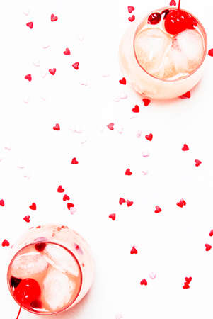 Pink alcoholic cocktail for Valentines day, two glasses, white background with sweet hearts, top view Archivio Fotografico