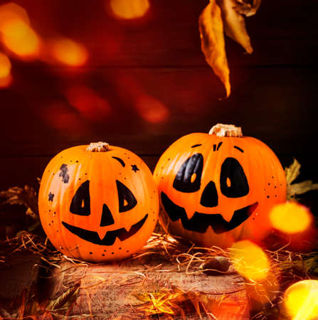Halloween festive composition with smiling pumpkins guards with lights, lantern, straw and fallen leaves on dark wooden background, rustic style, selective focus Stock Photo
