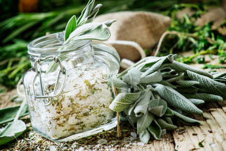 Sea salt, milled with sage in a glass jar, fresh herbs, vintage wooden background, selective focus Stock fotó