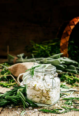 Sea salt with dried rosemary in a glass jar, vintage wooden background, selective focus Stock fotó