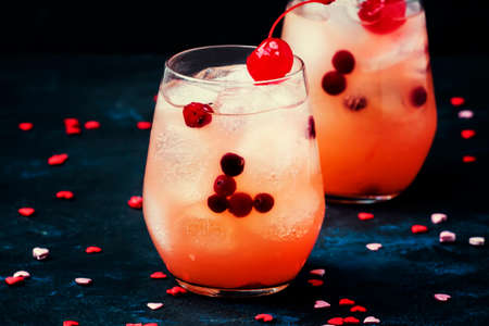 Festive alcoholic cocktail with red maraschino cherries for Valentines day, two glasses, black background with sweet hearts, selective focus Archivio Fotografico