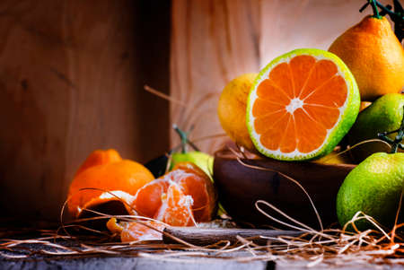 Cut green tangerines with orange pulp, vintage wooden background, selective focus