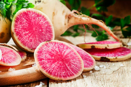 Slices of pink watermelon radish on a wooden table with parsley and dill, selective focus Banque d'images