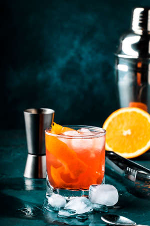 Orange Alcohol cocktail with red vermouth, bitter, soda, orange zest and ice, dark wooden bar counter background, bar tools, selective focus