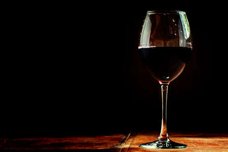 Chilled dry red wine in the glass. Dark vintage wood background. Low key, selective focus. Stock Photo