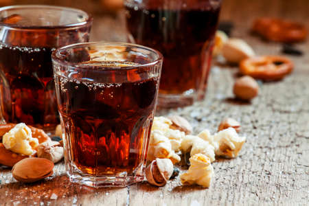 Cola glasses, sweet and savory snacks, old wooden table, unhealthy food, selective focus