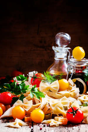 Italian food: Assorted dry pasta, herbs, garlic, red and yellow cherry tomatoes, jar with olive oil and balsamic vinegar, vintage wooden background, selective focus Archivio Fotografico