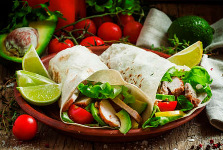 Fresh roll shawarma (doner) with meat, avocado, cherry tomatoes, peppers and lettuce on a clay plate, dark toned image, street food concept, selective focus