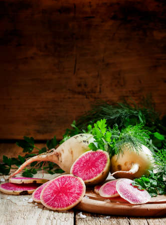 Slices of pink watermelon radish on a wooden table with parsley and dill, selective focus 写真素材