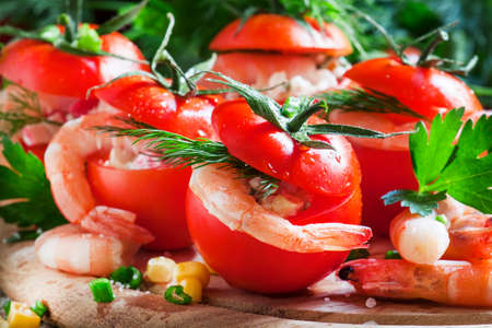 Tomatoes stuffed with shrimp meat and corn on a wooden plate, selective focus