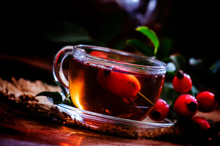 Healing black tea with wild rose berries in a glass cup. Vintage wooden background. Selective focus Banco de Imagens