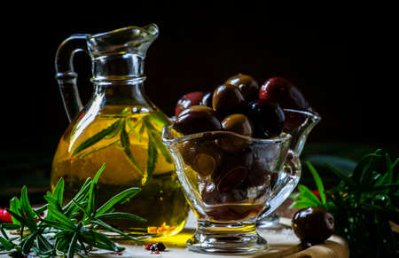 Greek olives in a glass bowl and oils, dark wood background, selective focus Stockfoto