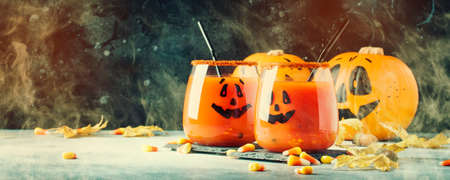 Halloween composition with festive red bloody drink and smiling pumpkins, with sweet corn and fallen leaves on dark background, selective focus Stok Fotoğraf