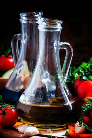 Olive oil and balsamic vinegar in pitchers, vegetables, herbs and spices, dark wood background, selective focus