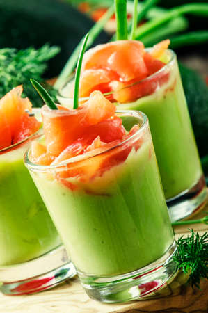 Appetizer with smoked salmon and avocado mousse, served in glasses, vintage wooden background, selective focus