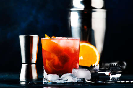 Garibaldi alcoholic cocktail with red bitter, orange juice, zest and ice. Dark blue background, bar tools, selective focus