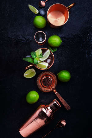 Preparation Moscow Mule cocktail with ginger beer, vodka, lime and ice. Copper bar tools. Black bar counter background. Top view. Copy space
