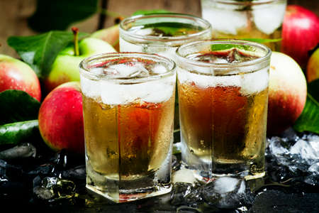 Cold apple juice with crushed ice, fresh apples with green leaves on a dark background, selective focus Zdjęcie Seryjne