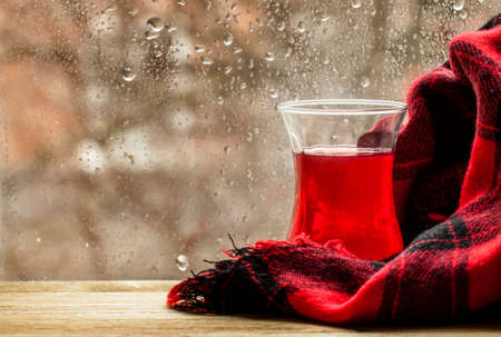 Red tea from China rose in the Islamic glass in the window on a rainy spring weather, selective focus
