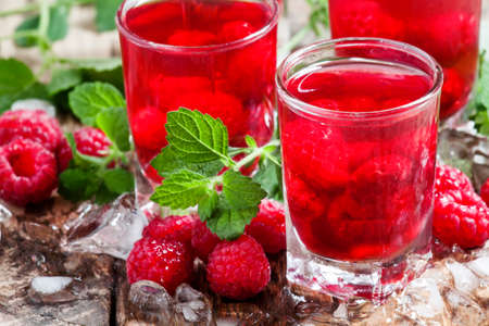 Refreshing raspberry drink with berries, ice and mint, selective focus