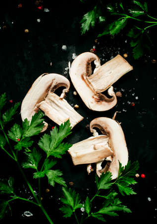 Food background slices of mushrooms, herbs and spices on a dark background, top view