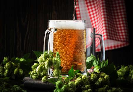 Glasses with czech light beer, dark night bar counter, hop cones and vine, selective focus Foto de archivo