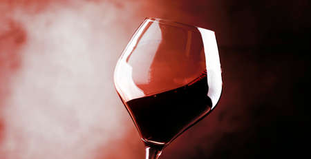 Red wine, splash in a glass, dry cabernet sauvignon, dark red background, defocused in motion image, shallow depth of field