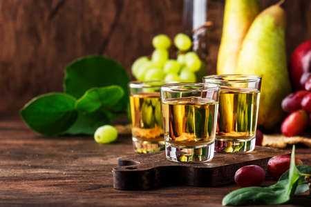 Rakija, raki or rakia - Balkan strong alcoholic drink brandy type based on fermented fruits, vintage wooden table, still life in rustic style, place for text