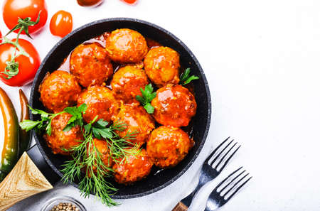 Meatballs with tomato sauce and spices in frying pan on white kitchen table background. Top view with copy space