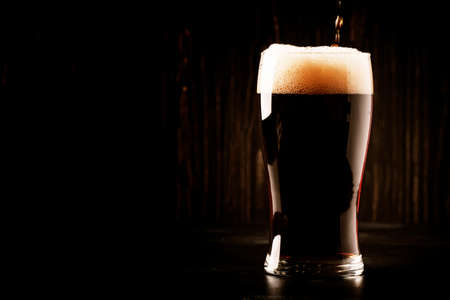 Dark english beer, ale or stout is poured into glass, dark bar counter, space for text, selective focus