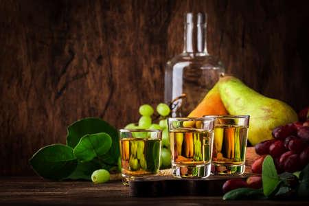 Rakija, raki or rakia - Balkan hard alcoholic drink or brandy from fermented fruits, old wooden table, still life, copy space Standard-Bild