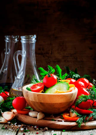 Salad with bell pepper, tomato, cucumber, garlic, herbs and olive oil in a wooden bowl, selective focus