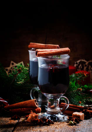 Mulled wine in large glasses for hot drinks in Christmas decorations with spices, pine cones and spruce paws, vintage wooden background, selective focus
