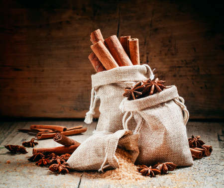 Spices for mulled wine: cinnamon, anise, brown cane sugar in bags made of burlap on an old wooden table in rustic style, selective focus