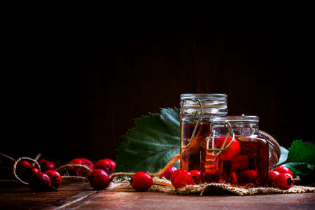 Medicinal alcoholic tincture of hawthorn berries in glass jars. Vintage wooden background, low key. Selective focus.