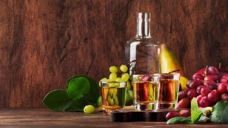 Rakija, raki or rakia - Balkan strong alcoholic drink brandy type based on fermented fruits, vintage wooden table, still life in rustic style, place for text
