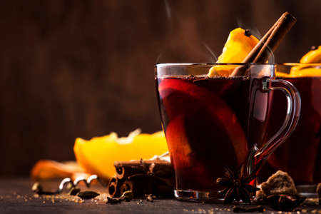 Hot mulled red wine with spices and fruits on wooden rustic table. Traditional Christmas hot drink, copy space
